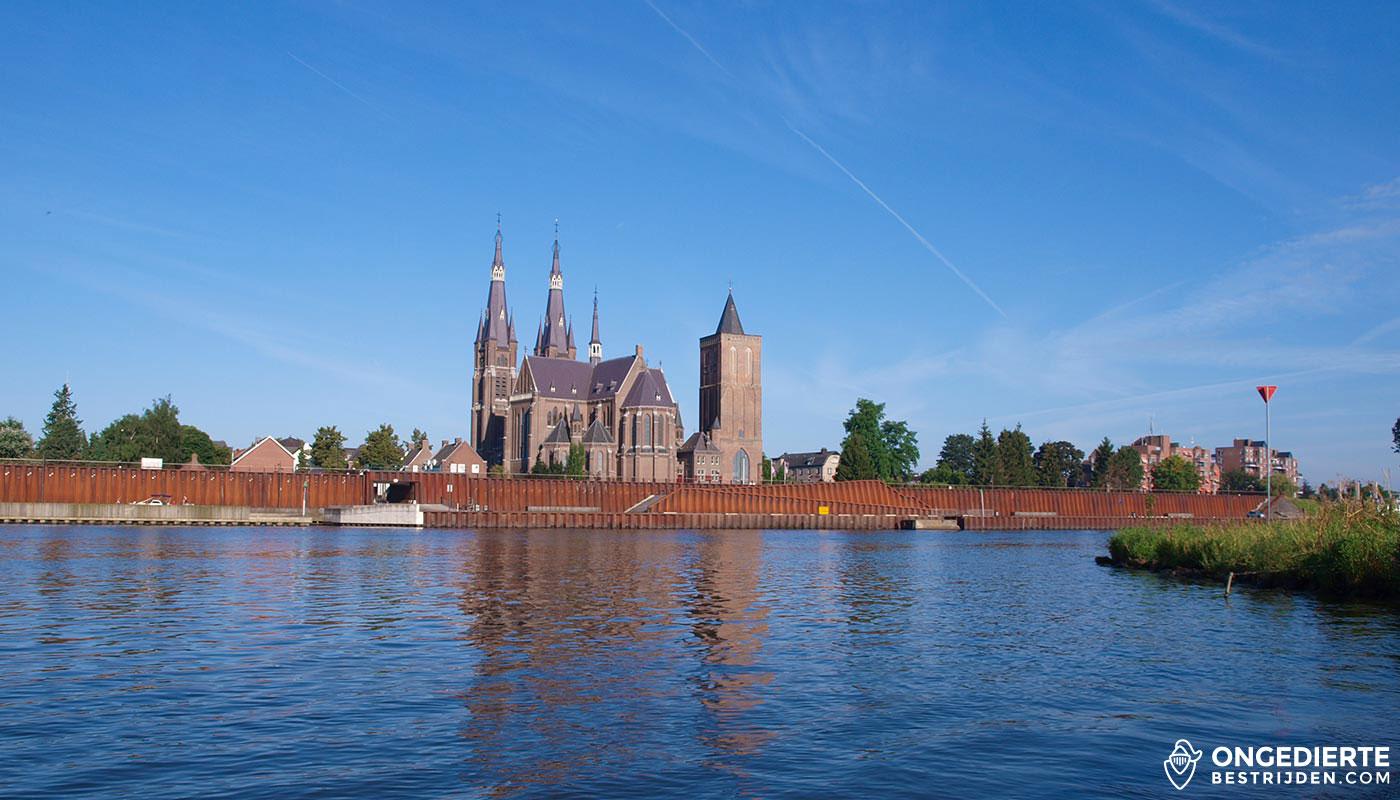 Kerk in Cuijk zichtbaar achter muur en huizen in Cuijk.