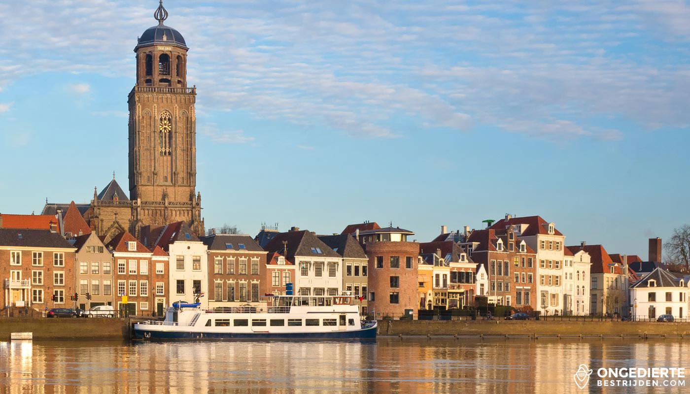 Skyline bij daglicht van Deventer met huizen, boten en kerk in beeld