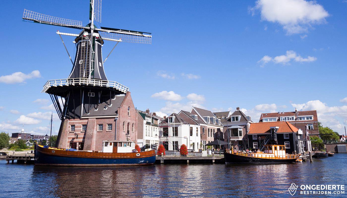 Oude Molen in Haarlem met woonhuizen, boten op voorgrond